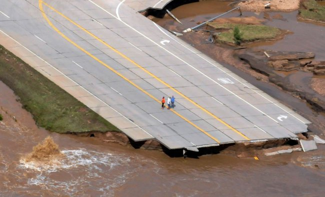 This Sept. 14, 2013, photo shows a small group of people investigating the road damage that...