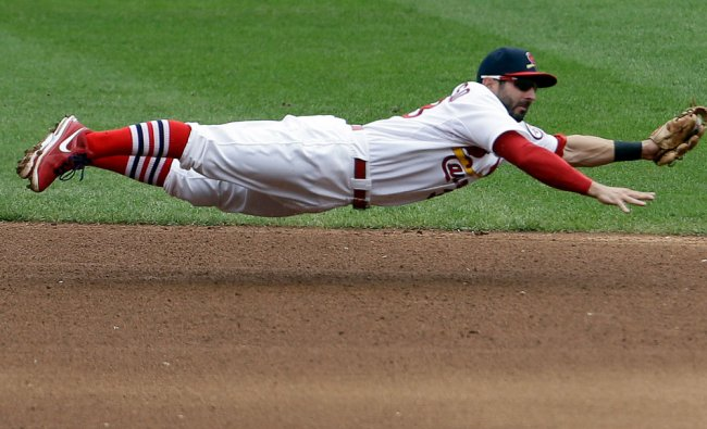 St. Louis Cardinals shortstop Daniel Descalso dives and stops a grounder hit by Seattle Mariners\'...