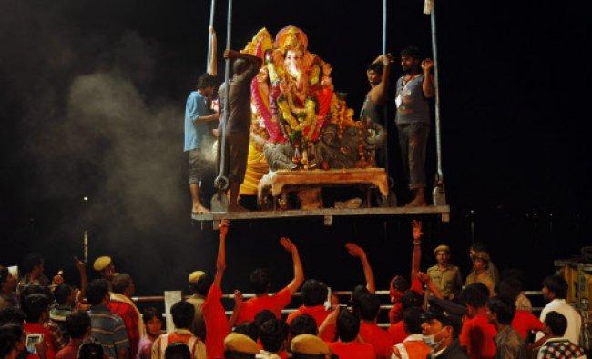 An idol of elephant-headed Hindu god Ganesha is lifted to be immersed in the Hussain Sagar Lake...