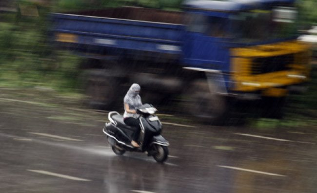 A woman rides a scooter with her face covered with a scarf to protect her from rain in Hyderabad...