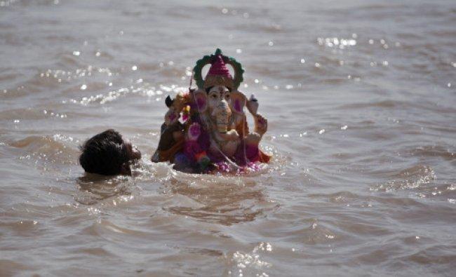 A devotee immerses an idol of elephant-headed Hindu god Ganesha in the Chenab River during Ganesh...