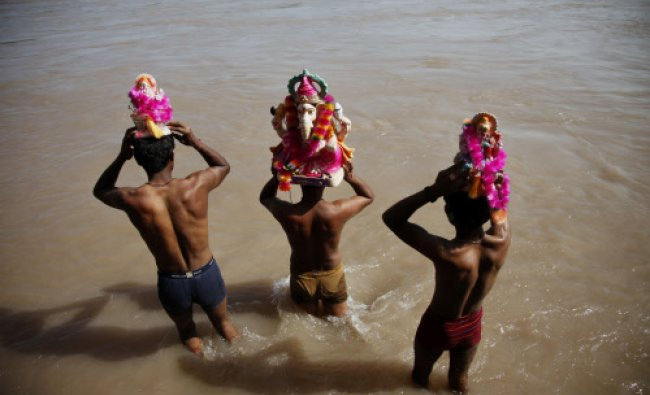 Devotees prepare to immerse idols of elephant-headed Hindu god Ganesha in the Chenab River during...