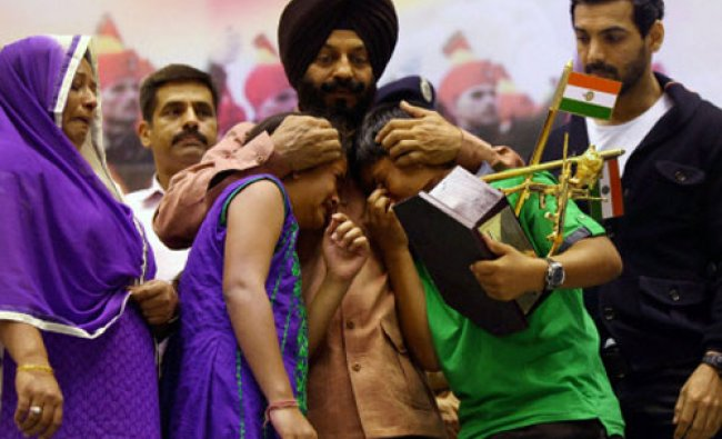 All India Anti Terrorist Front Chairman MS Bitta hugs the children of a war martyr while honoring...