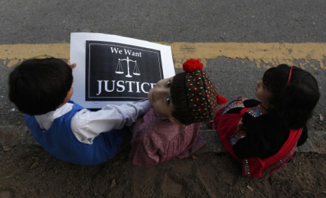 Children sit with a placard on a roadside during a protest by members of a civil society...
