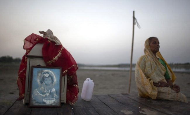 A woman sits in a cot beside an image of Hindu god Krishna as she watches other devotees...