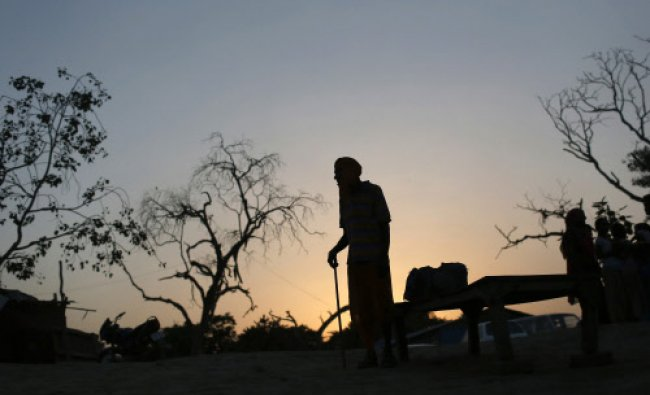 A man is silhouetted against the setting sun as he watches Hindu devotees carry an idol...