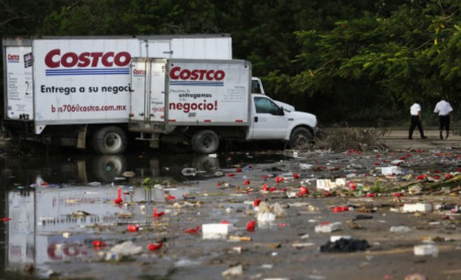 Trucks stand near floodwaters outside a store in Acapulco September 18, 2013. Looting broke out...