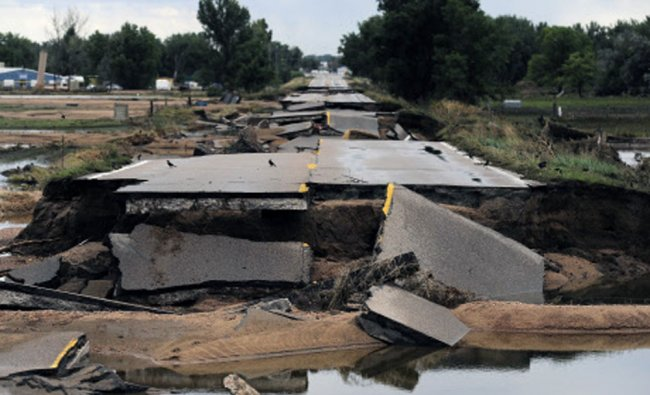 This photo shows flood damage to Old Highway 34 in Loveland, Colo., on Wednesday, Sept. 18, 2013.