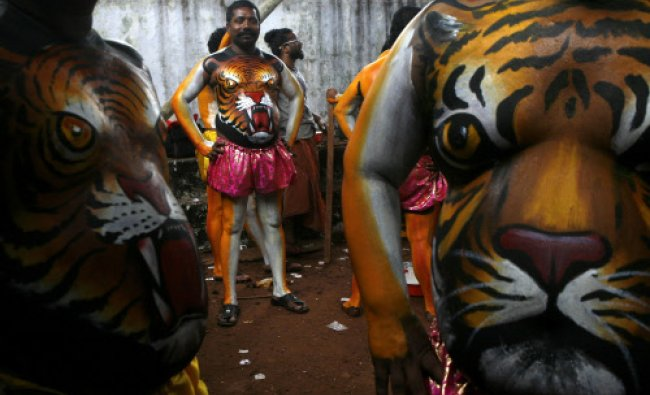 Artists, with painted bodies, wait to perform during the annual \'Pulikali\' or Tiger Dance...
