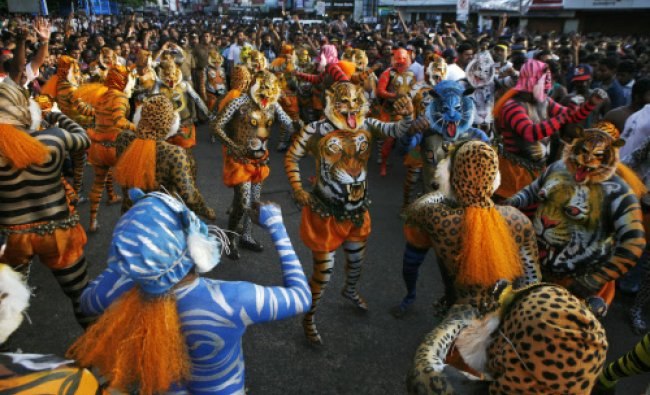 Artists with painted bodies and wearing masks perform the annual \'Pulikali\' or Tiger Dance...