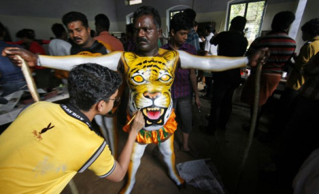 An artist stands to have his body painted to perform the annual \'Pulikali\' or Tiger Dance...