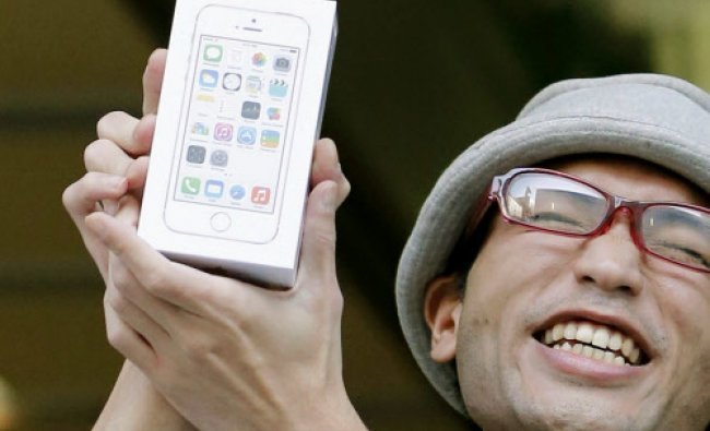 A customer shows off a new iPhone after he purchased at an Apple store in Tokyo Friday...