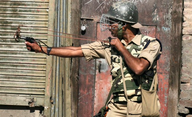 A security person uses a sling shot to disperse protesters in Srinagar ...