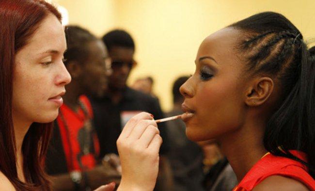 A Miami-based makeup artist applies makeup to a model backstage at Haiti Fashion Week 2013