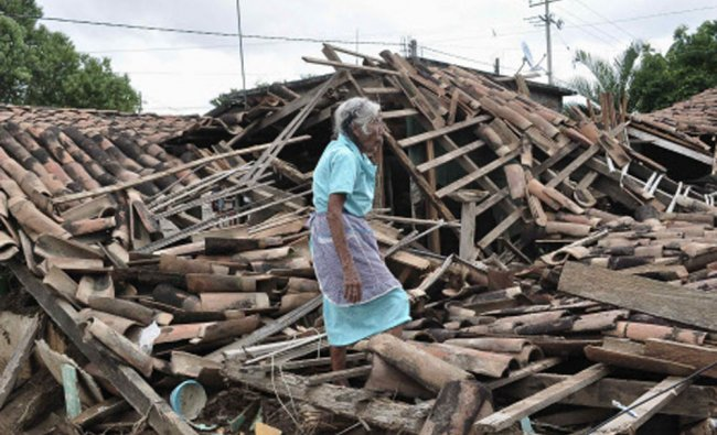 A woman stands amidst the debris of her destroyed home in Agua Caliente