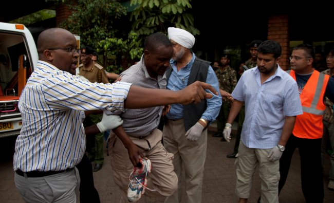 An injured person is helped on his arrival at the Aga Khan Hospital in Nairobi after an attack...