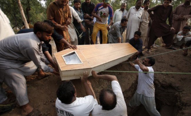 Relatives carry the casket of a man killed in Sunday\'s suicide attack on a church for burial at a...