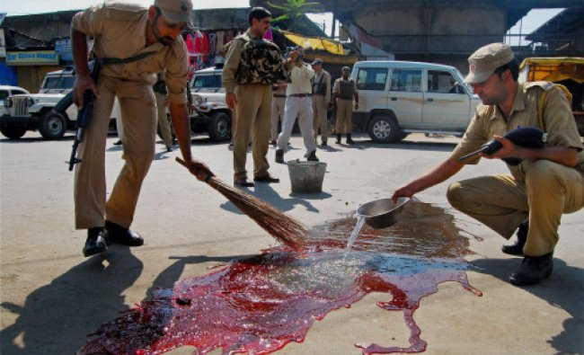 Police Personnel washing blood stains where two CISF personnel were killed by unidentified...