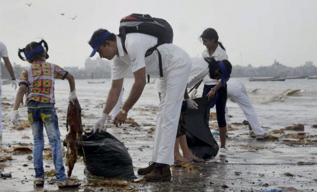 Coast guards with their family clean up the beach at Girgaum Chowpatty in Mumbai on Sunday....
