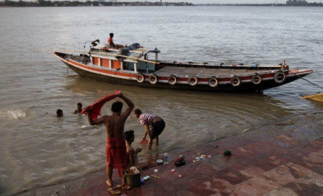 Locals take a bath on the banks of the Ganges river by a moored country boat in Kolkata, Sunday...