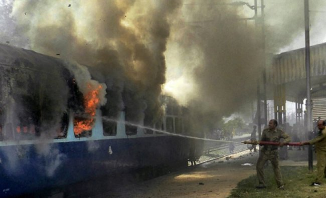 Fire personnel dousing the flames at a coach of Magadh Express which caught fire at Chausa Station..