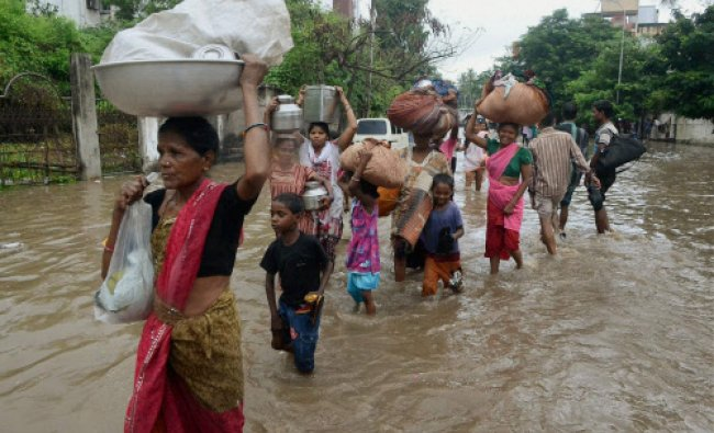 People wade through a flooded road with their household items to safer place after heavy rains in...