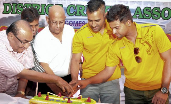 Indian cricket skipper Mahendra Singh Dhoni with cricketer Suresh Raina cutting a cake at the...