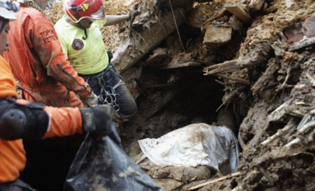 Rescue workers stand next to body recovered from site of mudslide at village of La Pintada