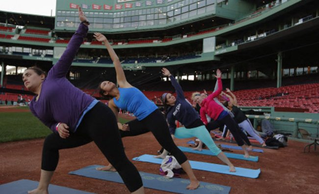 Participants take part in the first ever public yoga session at Fenway Park