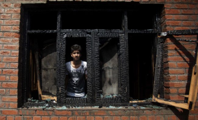 A Kashmiri boy looks out from the burnt window of his house after a fire in Srinagar, Tuesday...