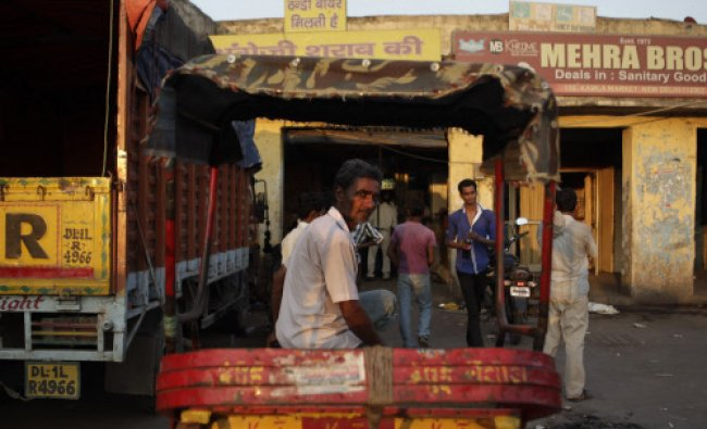 A cycle rickshaw puller awaits customers outside a wine shop in New Delhi, Monday, Sept. 23, 2013...