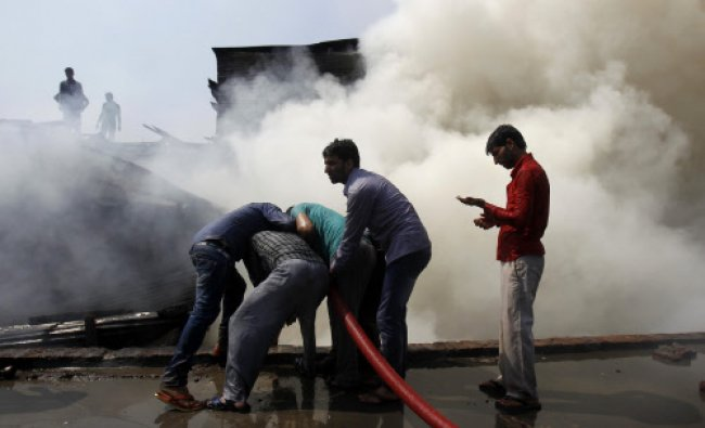 Residents hold a water hose as they try to douse a fire in downtown Srinagar September 24, 2013....