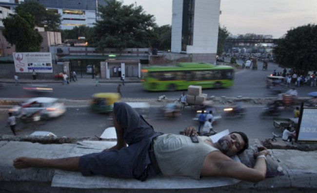 A daily wage laborer who lives in a make shift plastic structure on the roof of a building rests...