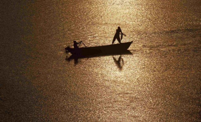 Girls are silhouetted against the rising sun as they fish in the waters of the Ganges river in...