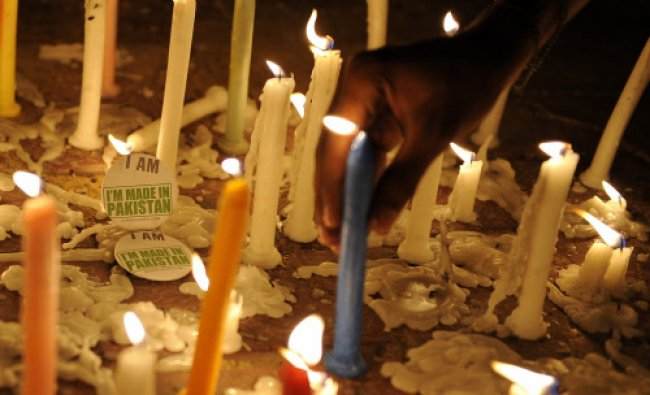 Members of civil society placed candles in front of an \'I\'m made in Pakistan\' badge during a...