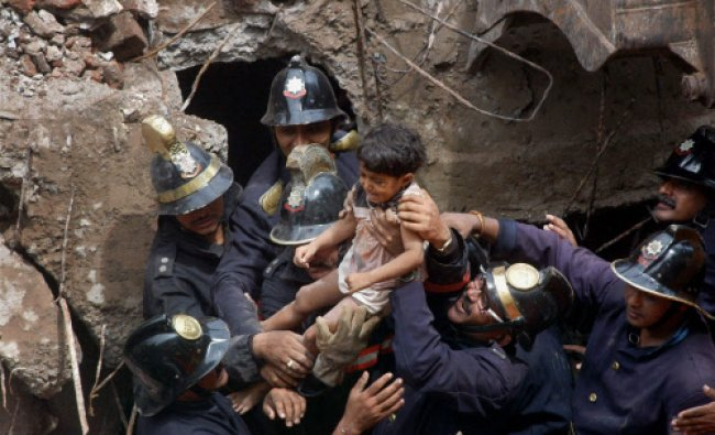Fire Brigade personnel rescue a boy after a BMC building collapsed at Brahmadev Khot Marg in...