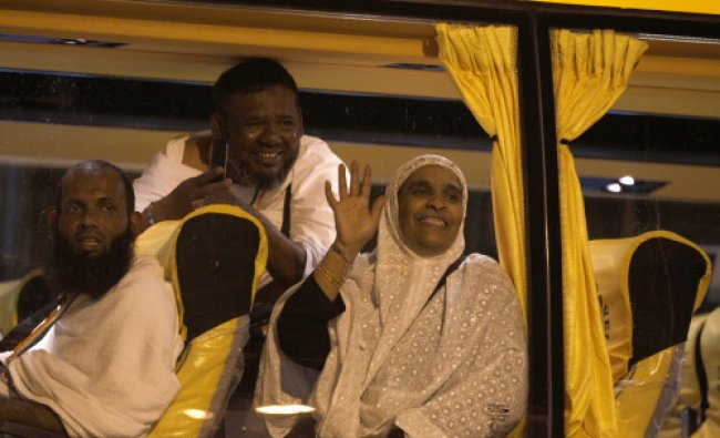 Hajj pilgrims wave to their relatives after boarding a bus as they leave for an annual pilgrimage to