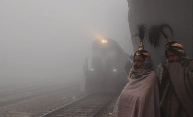 Passengers wait for the train on a foggy morning in Patiala on Tuesday. PTI Photo