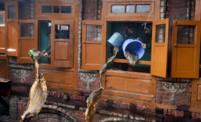 Kashmiris use buckets to remove water from a house damaged during fire in Srinagar, Tuesday ...