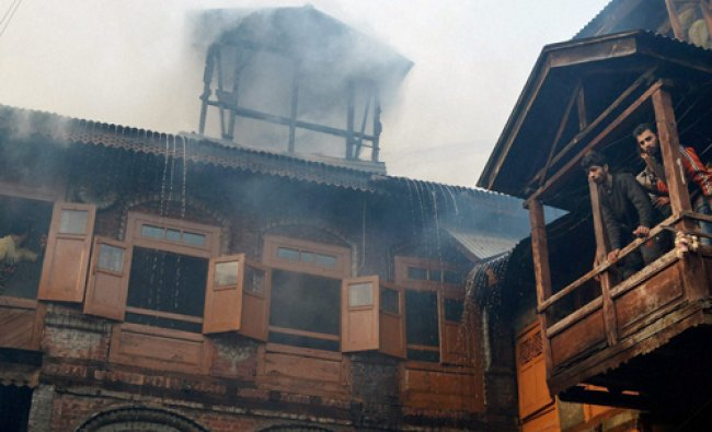 Smoke billowing out of a building where a fire broke out at Kawdara in Srinagar on Tuesday. PTI...