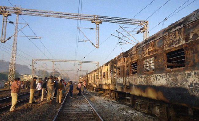 Police looking at the charred engines and coaches of Dongargarh-Raipur passenger train which...