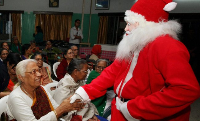 Santa Claus shaking hands with senior citizens during Christmas celebrations at an old age home...