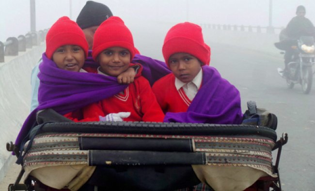 Children heading for school on a rickshaw in thick fog in Bathinda on Tuesday. PTI Photo