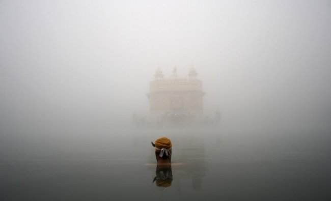 A Sikh devotee takes a holy bath in a sacred pond at the Golden Temple, the holiest Sikh shrine ...