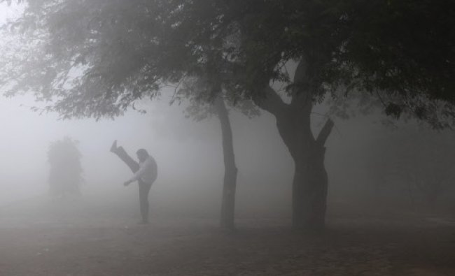 A man performs stretch exercises on a foggy morning in New Delhi, Wednesday, Dec. 18, 2013.