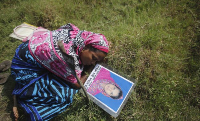 File photo of a woman mourning on the grave of her daughter after her body was identified at ...