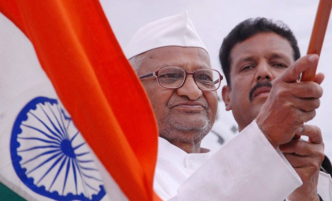 Anna Hazare waves a Tricolours before his supporters in Ralegan Sidhi after the passage of Lokpal .