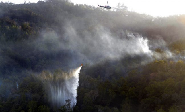 A helicopter makes a water drop on Pfeiffer Ridge above Fernwood in Big Sur, Calif., on Thursday...