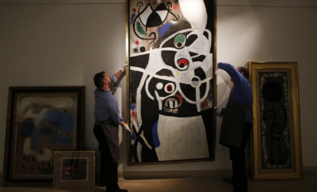 In this Thursday, Dec. 19, 2013 photo, auction house workers adjust Joan Miro\'s 1968 oil painting...