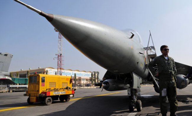 A pilot stands next to India\'s indigenously designed and developed combat aircraft Tejas at...